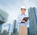 smiling businesswoman in helmet with clipboard - PhotoDune Item for Sale