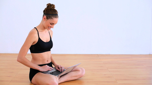 Thoughtful Woman Sitting On The Floor Using Laptop