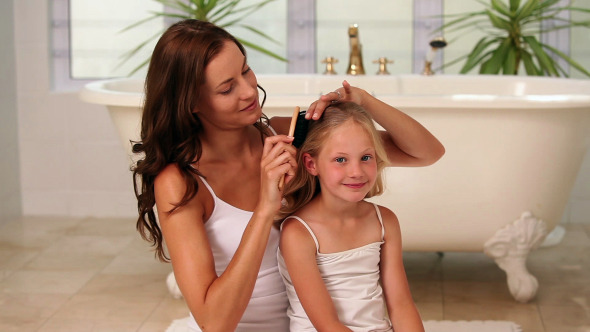 Mother Brushing Her Little Girls Hair