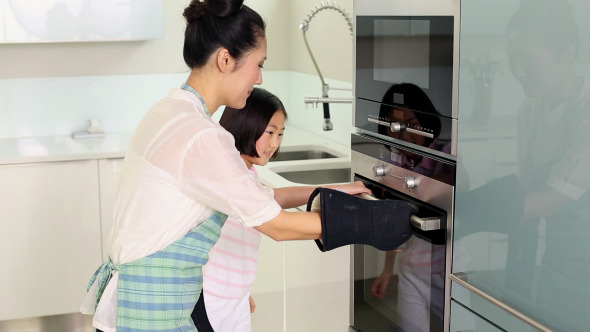 Mother Taking Baking Tray Out Of Oven