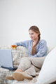 Woman sitting and holding a glass while looking on a laptop indoors