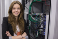 Girl standing in front of rack mounted servers in data storage facility