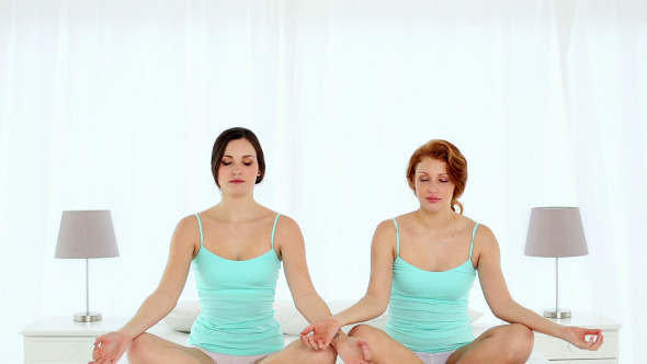 Peaceful Young Women Meditating In Lotus Position
