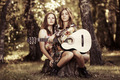 Hippie girls with guitar sitting on the stump - PhotoDune Item for Sale