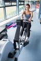 Brunette woman training on row machine in gym