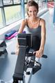 Brunette woman training hard on row machine