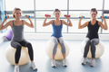 Three smiling women sitting on exercise balls and lifting weights in a gym