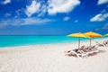 Lounge chairs & yellow umbrellas on tranquil Grace Bay Beach - PhotoDune Item for Sale