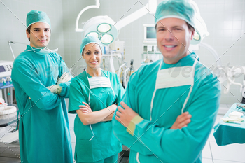 Smiling surgeons looking at camera with crossed arms in an operating theatre - PhotoDune Item for Sale