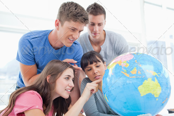 Four smiling students around a globe as two of them point to places in the world - PhotoDune Item for Sale
