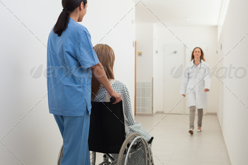 Nurse pushing patient in wheelchair with doctor approaching in hospital corridor - PhotoDune Item for Sale