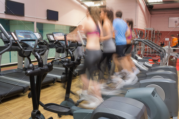 People working out on on step machines at speed in gym - PhotoDune Item for Sale