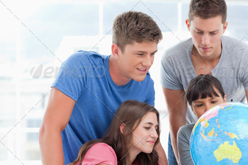 A group looking at places on the globe of the world - PhotoDune Item for Sale