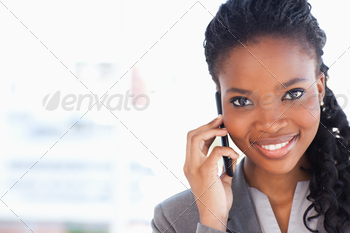Smiling businesswoman looking ahead while talking on a phone - PhotoDune Item for Sale