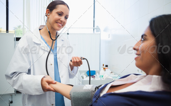 Doctor checking female patients blood pressure in hospital room - PhotoDune Item for Sale