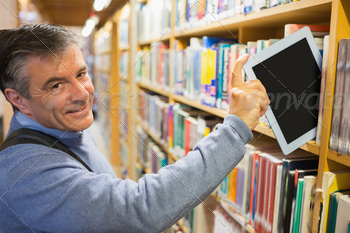 Smiling man taking a tablet pc from the shelves in library - PhotoDune Item for Sale