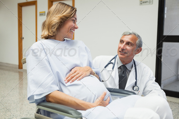 Doctor is talking to a pregnant woman in hospital corridor - PhotoDune Item for Sale