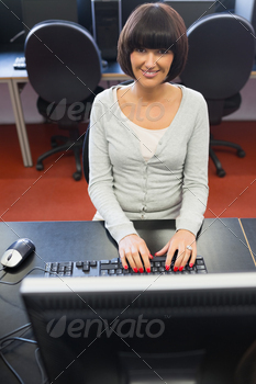 Smiling woman typing on the computer in the class - PhotoDune Item for Sale