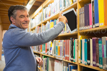 Man pulling out a tablet pc from the shelves in the library - PhotoDune Item for Sale