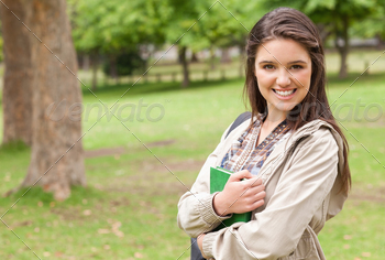 Portrait of a young student holding textbook while posing in a park - PhotoDune Item for Sale