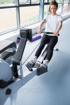 Energetic woman training on row machine in gym - PhotoDune Item for Sale