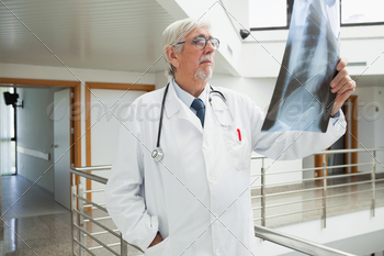 Doctor standing on the corridor looking at a x-ray in a hospital - PhotoDune Item for Sale