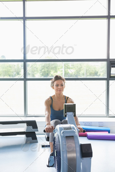 Woman training on row machine in a gym - PhotoDune Item for Sale