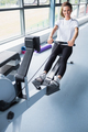 Smiling  woman training on row machine in gym