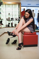 Woman sitting in a boutique trying on shoes