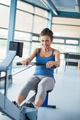 Woman training ambitiously on row machine in gym