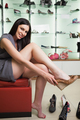 Woman is sitting in a boutique trying shoes and smiling