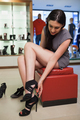 Woman sitting in a boutique in the city trying shoes