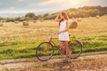 Beautiful woman old bicycle with flowers in wheat field  - PhotoDune Item for Sale