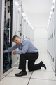 Technician kneeling while repairing the server case in a data center