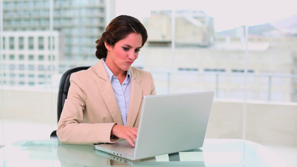 Concentrated Attractive Businesswoman Using Laptop