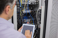 Man doing server maintenance with tablet pc in data center