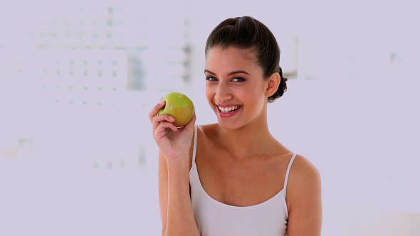 Amused Beautiful Woman Smelling And Showing Apple