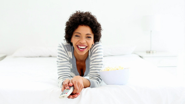 Cute Woman Lying On Bed Watching Tv