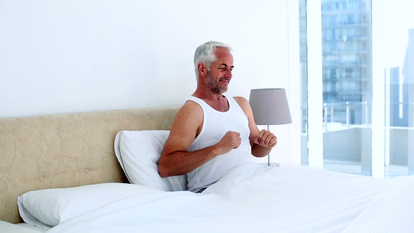 Smiling Man Yawning And Stretching Sitting On Bed