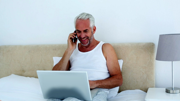 Laughing Man Using Laptop While On The Phone
