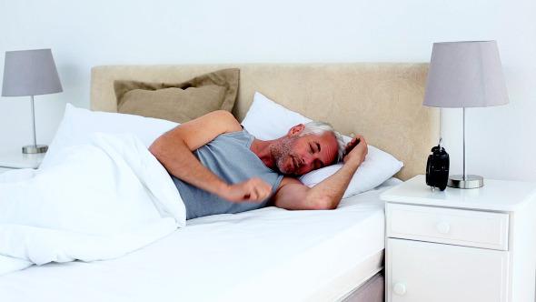 Groggy Man Waking Up And Looking At Alarm Clock