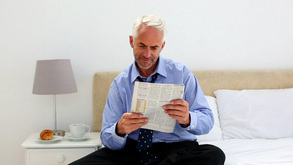 Businessman Sitting On Bed Reading Newspaper