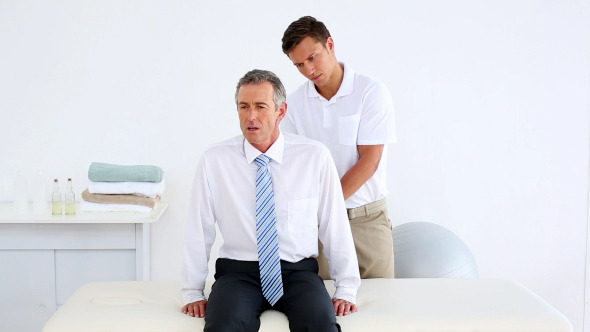 Stressed Businessman Getting His Back Checked