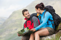 Couple resting after hiking uphill and holding map in the countryside