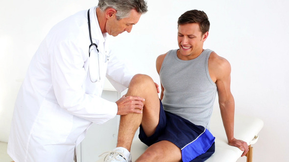 Mature Doctor Checking Sportsmans Injured Knee