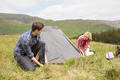 Happy couple pitching their tent in the countryside - PhotoDune Item for Sale