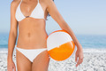Sexy female body in white bikini with beach ball on the beach - PhotoDune Item for Sale
