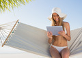 Cheerful blonde sitting on hammock using tablet pc at the beach - PhotoDune Item for Sale