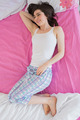 Brunette in pajamas lying on bed and looking away in bedroom at home - PhotoDune Item for Sale