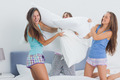 Friends having pillow fight at home at slumber party - PhotoDune Item for Sale